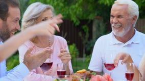 Família amigável que comunica-se e que ri tendo o passatempo exterior do prazer do almoço vídeos de arquivo