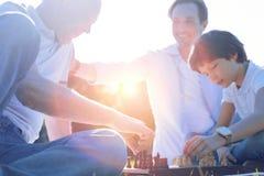 Família amigável que joga a xadrez junto Foto de Stock