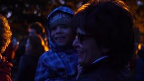 A família anda na noite no parque na margem Luzes brilhantes A avó guarda a criança em seus braços video estoque