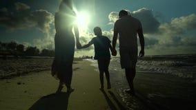 A família anda na praia Os pais andam com seu filho ao longo do litoral Estão felizes O sol brilha brilhantemente vídeos de arquivo