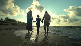 A família anda na praia Os pais andam com seu filho ao longo do litoral Estão felizes O sol brilha brilhantemente video estoque