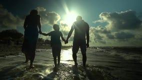 A família anda na praia Os pais andam com seu filho ao longo do litoral Estão felizes O sol brilha brilhantemente filme