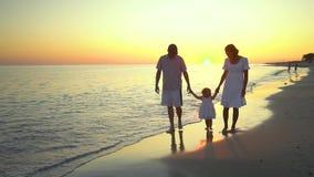 A família anda na praia Os pais andam com sua filha pequena ao longo do litoral Guardaram as mãos Estão felizes filme