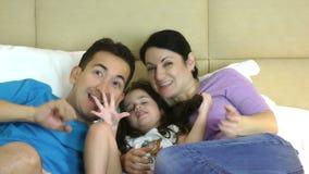 Família animado que olha a tevê na cama no quarto vídeos de arquivo