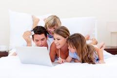 Família Animated que compra em linha o encontro para baixo na cama foto de stock