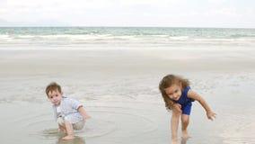 A família, as crianças, o irmão e a irmã novos jogam perto da família feliz da costa do oceano, andando ao longo do seacoast vídeos de arquivo