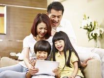 Família asiática com as duas crianças que usam a tabuleta digital junto Imagens de Stock Royalty Free