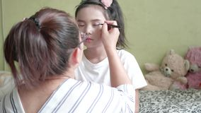 Família asiática com a mãe que faz a composição a sua menina na sala filme