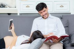 A família asiática dos pares que usa uma tabuleta em casa, a mãe nova está grávida Fotos de Stock Royalty Free