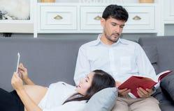 A família asiática dos pares que usa uma tabuleta em casa, a mãe nova está grávida no sofá Foto de Stock