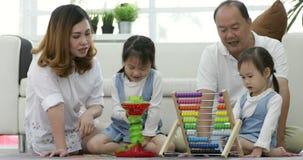 Família asiática feliz com as duas filhas que jogam em casa video estoque