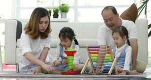 Família asiática feliz com as duas filhas que jogam em casa filme