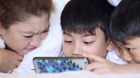 A família asiática feliz está jogando na tabuleta, sorrir, colocando na cama video estoque