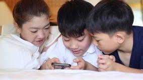 A família asiática feliz está jogando na tabuleta, sorrir, colocando na cama vídeos de arquivo