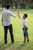 a fam?lia asi?tica feliz, os pais e suas crian?as d?o altamente cinco no parque junto filho de apoio do pai fora Ajuda do apoio foto de stock