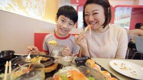 Família asiática feliz que come o sushi em um restaurante com cara do sorriso filme