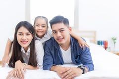 Família asiática feliz que encontra-se em uma cama fotos de stock
