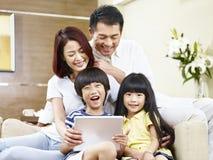 Família asiática feliz que usa a tabuleta digital junto foto de stock royalty free