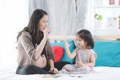 Família asiática feliz Relaxi grávido do abraço da filha da mãe e do bebê Fotografia de Stock Royalty Free