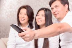Família asiática na tevê com telecontrole fotografia de stock