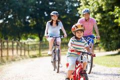 Família asiática no passeio do ciclo no campo imagem de stock