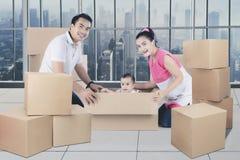 Família asiática nova que tem o divertimento que desembala caixas foto de stock royalty free