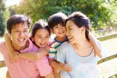 Família asiática que aprecia a caminhada no campo do verão