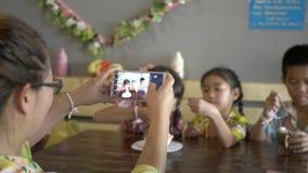 Família asiática que come o gelado e que toma o selfie com o smartphone na sala da cozinha video estoque