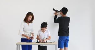 Família asiática que cortam o papel preto na forma do bastão, a seguir eles que colam a na parede, preparando-se para o festival  video estoque