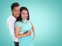 Família bonita durante a maternidade sobre o fundo da cor da hortelã fotos de stock royalty free