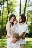 A família bonita e amigável está tendo o resto no parque O paizinho e a mamã estão guardando a filha nos braços e no aperto seus foto de stock royalty free