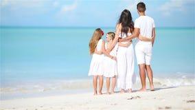 Família bonita feliz na praia branca filme