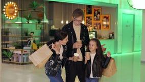 Família bonita feliz que guarda sacos de compras e copos com café na alameda video estoque
