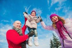 Família bonita nova no divertimento brilhante do inverno da roupa que salta e que corre, neve, estilo de vida, feriados de invern Fotografia de Stock