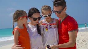 Família bonita nova que toma o retrato do selfie na praia filme