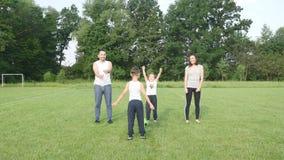 Família bonita que faz os empurrões físicos exteriores A família inclina e ostenta exercícios no campo de futebol na grama video estoque