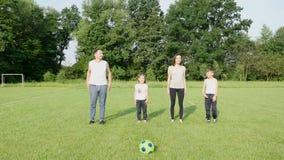 Família bonita que faz os empurrões físicos exteriores A família inclina e ostenta exercícios no campo de futebol na grama filme