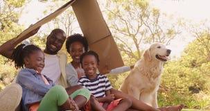 A família bonito está sentando-se no parque com um cão filme