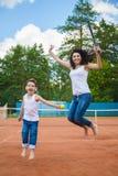 Família bonito ou mãe e filho que jogam o tênis e que levantam no tribunal exterior imagem de stock royalty free