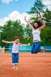 Família bonito ou mãe e filho que jogam o tênis e que levantam no tribunal exterior foto de stock