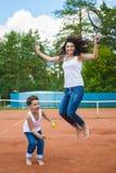 Família bonito ou mãe e filho que jogam o tênis e que levantam no tribunal exterior imagens de stock