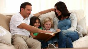Família bonito que lê um livro video estoque