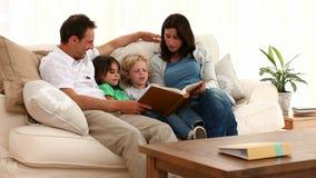 Família bonito que olha um álbum filme
