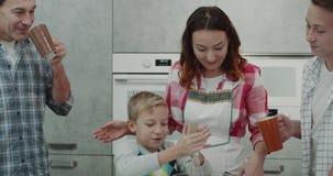 Família bonito que prepara junto o café da manhã, rapaz pequeno que mistura todos os ingredientes com um misturador da mão em uma video estoque