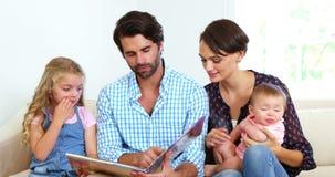 Família bonito que senta-se em um sofá e que olha um livro junto video estoque
