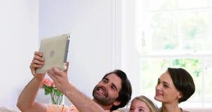 Família bonito que sorri e que toma uma foto com uma tabuleta filme