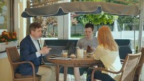 A família bonito senta-se no terraço de sua casa e bebe-se o café video estoque