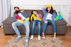 Família cansado família esgotada após ter limpado a casa produtos de limpeza cansados da posse da família Matriz, pai e filha fotos de stock royalty free