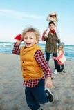 A família caucasiano branca, mãe com três crianças caçoa o jogo dos planos de papel, correndo na praia do mar do oceano no por do Foto de Stock Royalty Free
