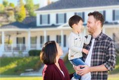 Família caucasiano e chinesa da raça misturada nova na frente da casa feita sob encomenda foto de stock